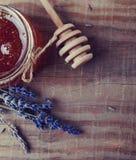 Il miele in un barattolo, in un cucchiaio del miele e in un lavendre di vetro fiorisce sul wo Fotografie Stock Libere da Diritti