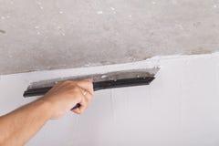 Il miglioramento della Camera dal lavoratore mette lo strato di finitura dello stucco su Th Fotografie Stock