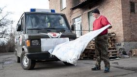 Il militare pulisce dopo la riparazione dell'ambulanza Fotografia Stock