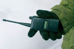Il militare sta tenendo un walkie-talkie fotografia stock