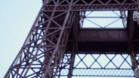 Il mimo in cappello rosso e la camicia spogliata compaiono dalla destra al fondo della torre Eiffel stock footage