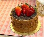 Il mini dolce di cioccolato di Scrumptous decorato ornately con i riccioli del cioccolato e della glassa ed ha lustrato le fragol fotografie stock