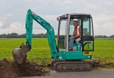Il mini escavatore sta spostando il terreno Fotografie Stock Libere da Diritti