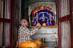 Il ministro del tempio indù esamina le decorazioni per l'altare Fotografia Stock