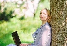 Il minuto per si rilassa Lavoro della ragazza con il computer portatile in parco sedersi su erba Tecnologia di istruzione e conce immagine stock