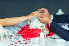 Il a mis ses anneaux de mariage sur son doigt Le marié a mis un anneau sur le doigt à lui beau Jeune femme souriant regardant la  images libres de droits