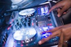 Il miscelatore del DJ con le mani del DJ fa la musica con le luci blu Immagine Stock