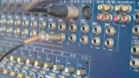 Il miscelatore pluged in microfono ed in presa con molti bottoni Fotografie Stock
