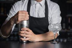 Il mixologist del barista tiene l'agitatore sul contatore della barra vicino a vetro immagini stock libere da diritti