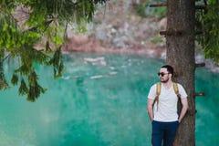 Il modello barbuto dell'uomo posa accanto ad un lago verde dell'acqua immagine stock libera da diritti