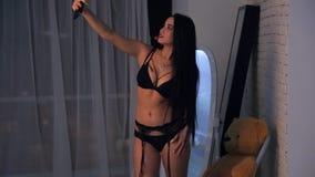 Il modello in biancheria nera fa il selfie accanto allo specchio in studio stock footage