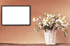 Il modello bianco in bianco della struttura con la camomilla fiorisce in canestro di bambù Fotografie Stock