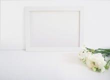 Il modello in bianco bianco della struttura di legno con il ranuncolo ed il narciso persiani fiorisce la menzogne sulla tavola bi Immagine Stock Libera da Diritti