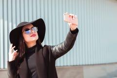Il modello castana alla moda indossa il cappello e gli occhiali da sole alla moda, Tak Fotografia Stock
