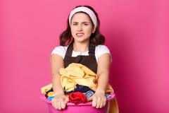 Il modello castana insoddisfatto ribaltamento posa isolato sopra fondo rosa, tenendo i vestiti sporchi con le mani, stancarsi del fotografia stock