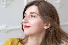 Il modello con il naso guarda fuori la finestra Fotografia Stock