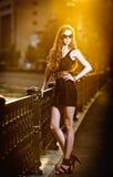 Il modello di moda sulla via con gli occhiali da sole ed il nero di short si vestono Fotografie Stock Libere da Diritti