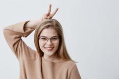 Il modello femminile adorabile sveglio in occhiali esamina allegro la macchina fotografica, gesti con le dita, ha espressione fel Immagini Stock