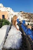 Il modello femminile biondo della bella sposa in vestito da sposa stupefacente posa sull'isola di Santorini in Grecia Immagini Stock