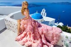 Il modello femminile biondo della bella sposa in vestito da sposa stupefacente posa sull'isola di Santorini in Grecia Fotografie Stock Libere da Diritti