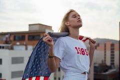 Il modello femminile biondo sostiene la bandiera americana fotografia stock libera da diritti