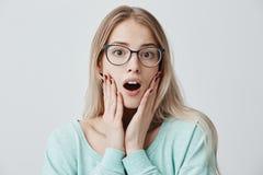 Il modello femminile biondo stupito con gli occhiali tiene la bocca ampiamente aperta, i sembrare stupiti, tiene le mani sulla gu Fotografie Stock