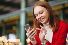 Il modello femminile piacevole del positivo usa i dati del telefono cellulare, usa l'applicazione di chiacchierata, tiene il tele immagine stock