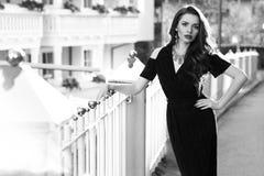 Il modello femminile splendido in vestito nero con ritaglio mette Immagini Stock