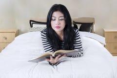 Il modello grazioso legge un libro sulla camera da letto Fotografia Stock Libera da Diritti
