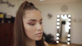 Il modello ha un trucco dal truccatore nel salone di bellezza Primo punto di vista della persona Modello della testarossa con le  video d archivio
