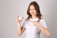 Il modello indica il dito al bicchiere di latte Fine in su Priorità bassa bianca Fotografia Stock