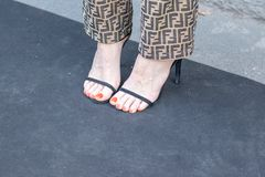 Il modello indossa un paio dei pantaloni di Fendi e un paio delle scarpe tallonate nere immagine stock