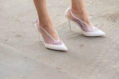 Il modello indossa un paio delle scarpe tallonate bianche e trasparenti immagini stock