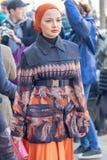 Il modello indossa un vestito variopinto e un copricapo arancio fotografie stock libere da diritti