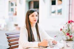 il modello mixed bevente del caffè cinese caucasico attraente del caffè all'aperto corre la donna del marciapiede fotografie stock libere da diritti