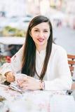 il modello mixed bevente del caffè cinese caucasico attraente del caffè all'aperto corre la donna del marciapiede immagine stock