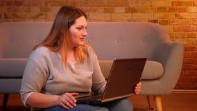 Il modello più di dimensione si siede sul pavimento che parla nel videochat sul computer portatile che è premuroso in atmosfera d archivi video