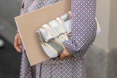 Il modello porta una borsa bianca e dorata in sua mano fotografia stock libera da diritti