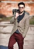 Il modello sexy dell'uomo di modo ha vestito la tenuta elegante una borsa Fotografia Stock