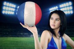 Il modello sexy tiene un pallone da calcio in stadio Immagine Stock