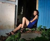 Il modello si siede davanti alla casa di rovina Immagine Stock