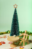 Il modello si siede sulla sedia verde con l'albero di Natale isolato su fondo verde molle fotografie stock libere da diritti