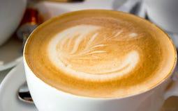 Il modello sul caffè in una tazza bianca Fotografia Stock