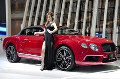 Il modello tailandese si leva in piedi vicino ad un convertibile di Bentley Immagine Stock Libera da Diritti