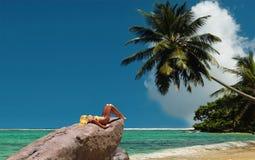 Il modello tunning sulla roccia. Spiaggia reale. Fotografie Stock