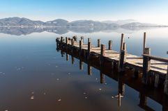 Il molo sul lago, ancora innaffia e la riflessione Immagini Stock