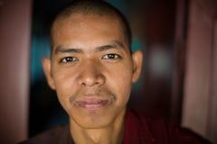 Il monaco birmano in abito rosso posa per il ritratto al monastero di Maha Gandaryon Immagini Stock