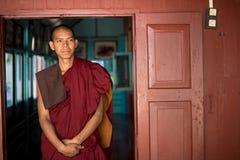 Il monaco birmano in abito rosso posa per il ritratto al monastero di Maha Gandaryon Fotografie Stock Libere da Diritti