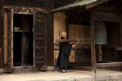 Il monaco buddista suona una campana Fotografia Stock