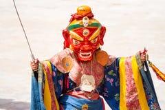 Il monaco con la spada esegue un ballo mascherato e costumed religioso di mistero di buddismo tibetano immagine stock libera da diritti